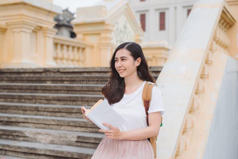Mujer joven hermosa feliz con la mochila y el libro que se sientan en las escaleras al aire libre foto de archivo libre de regalías