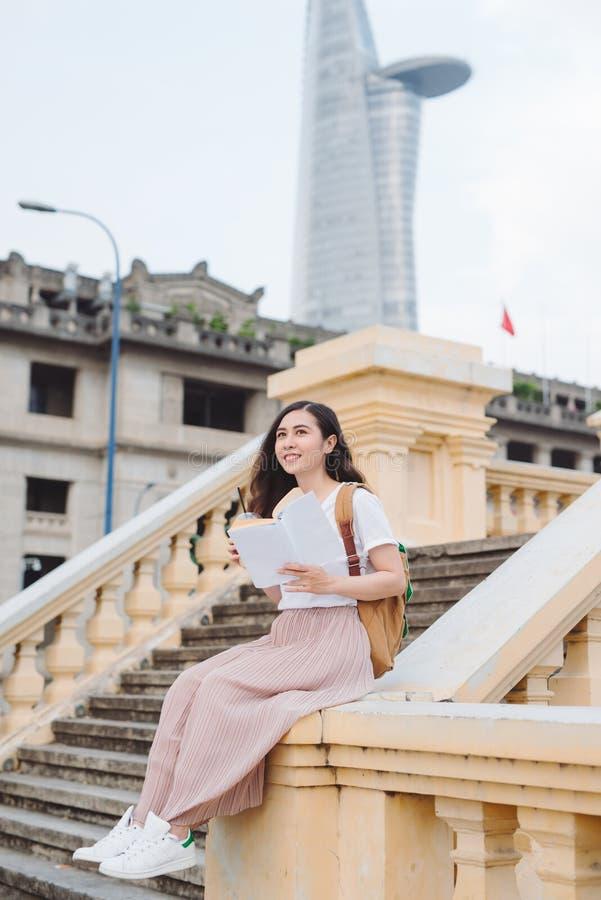 Mujer joven hermosa feliz con la mochila y el libro que se sientan en las escaleras al aire libre fotografía de archivo