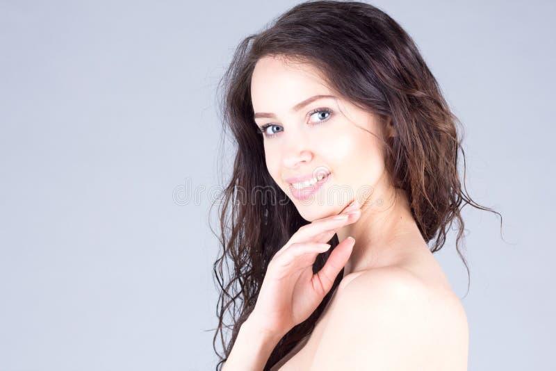 Mujer joven hermosa feliz con los ojos azules grandes y el pelo rizado que sonríe con los dientes Cara hermosa de la mujer fotografía de archivo libre de regalías