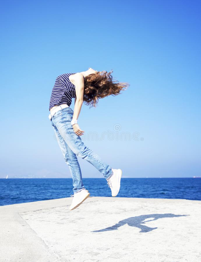 Mujer joven hermosa feliz que salta en el embarcadero contra el azul foto de archivo
