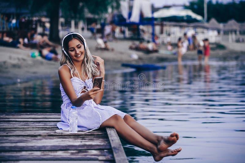 Mujer joven hermosa gozar mientras que música que escucha en la playa fotos de archivo libres de regalías