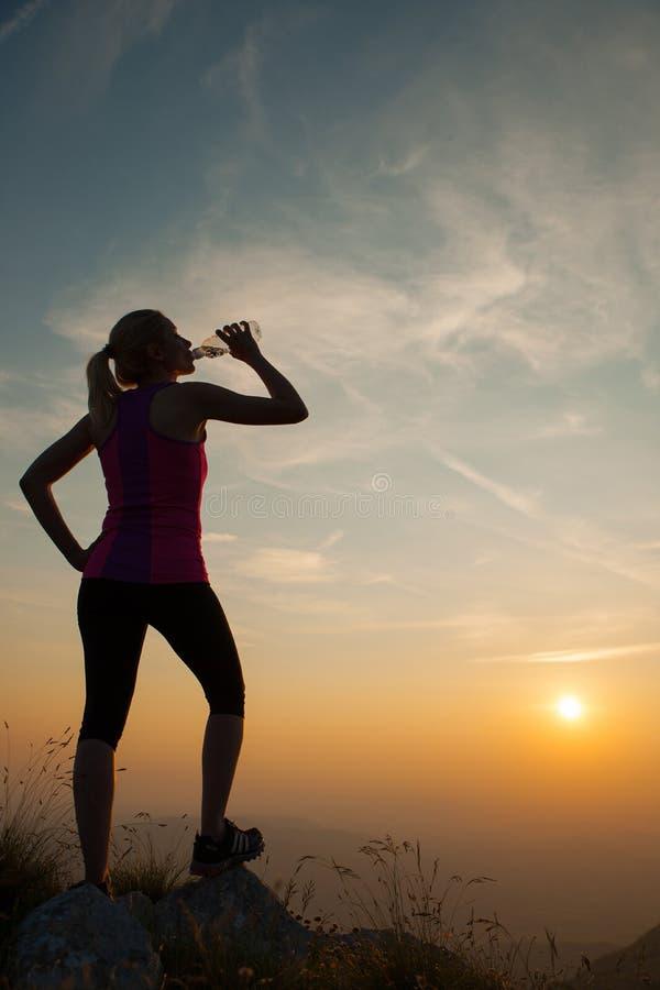 Mujer joven hermosa observando puesta del sol con la botella de agua foto de archivo
