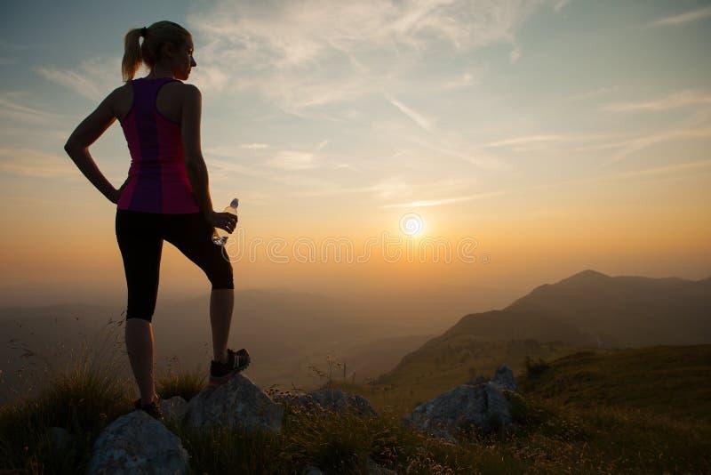 Mujer joven hermosa observando puesta del sol después de correr en un mountian foto de archivo