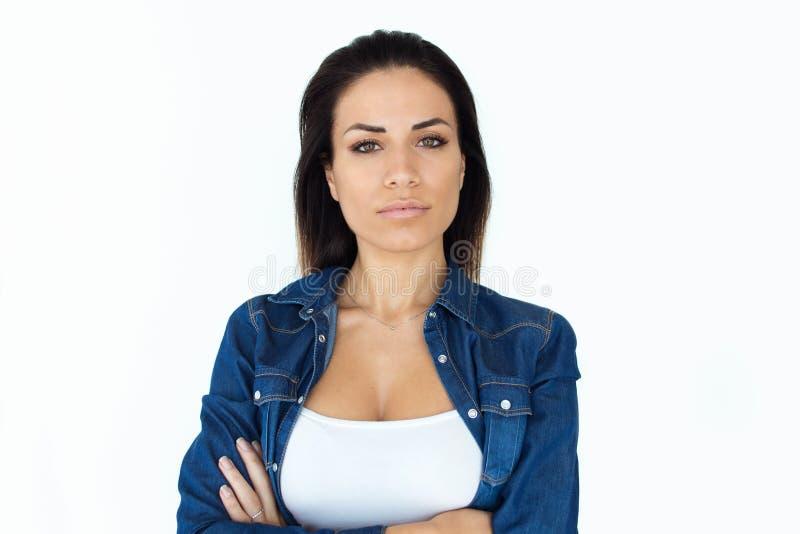 Mujer joven hermosa orgullosa que mira la cámara sobre el fondo blanco imagen de archivo