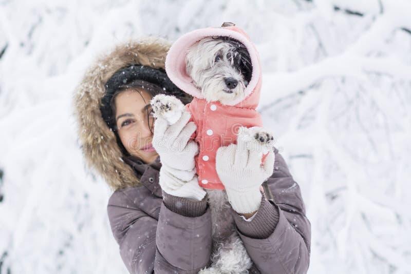 Mujer joven hermosa que abraza su pequeño perro blanco en el bosque del invierno tiempo que nieva imagen de archivo libre de regalías