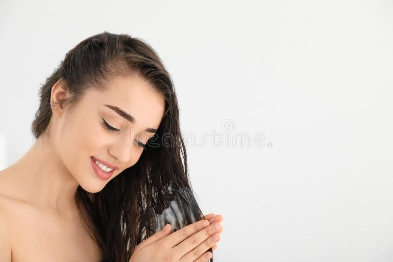 Mujer joven hermosa que aplica el acondicionador de pelo contra el fondo blanco fotos de archivo