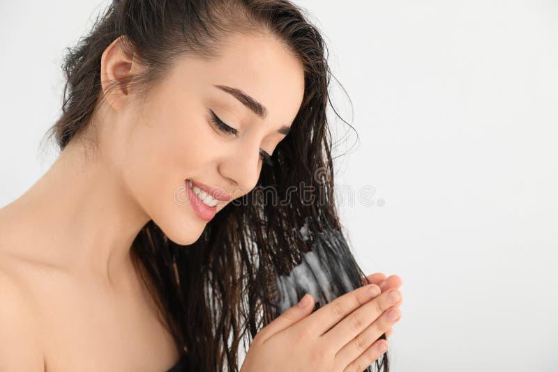 Mujer joven hermosa que aplica el acondicionador de pelo contra el fondo blanco foto de archivo