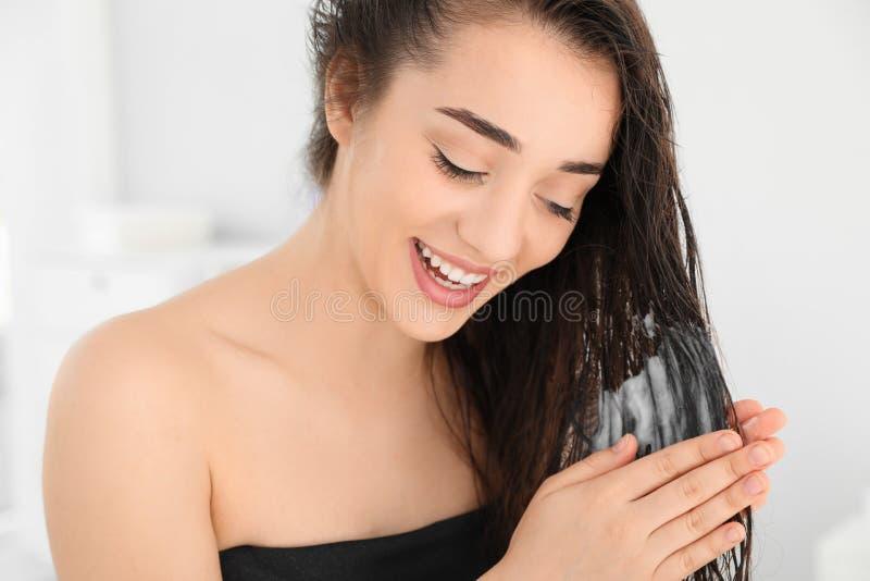 Mujer joven hermosa que aplica el acondicionador de pelo imágenes de archivo libres de regalías