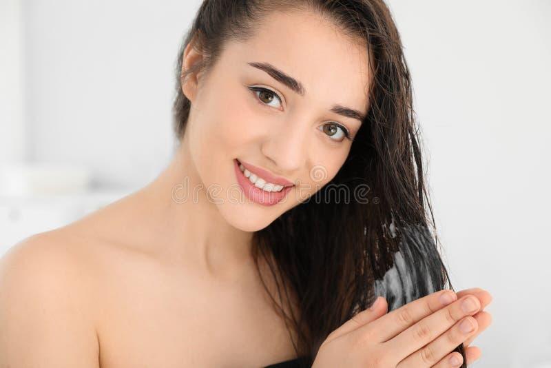 Mujer joven hermosa que aplica el acondicionador de pelo foto de archivo
