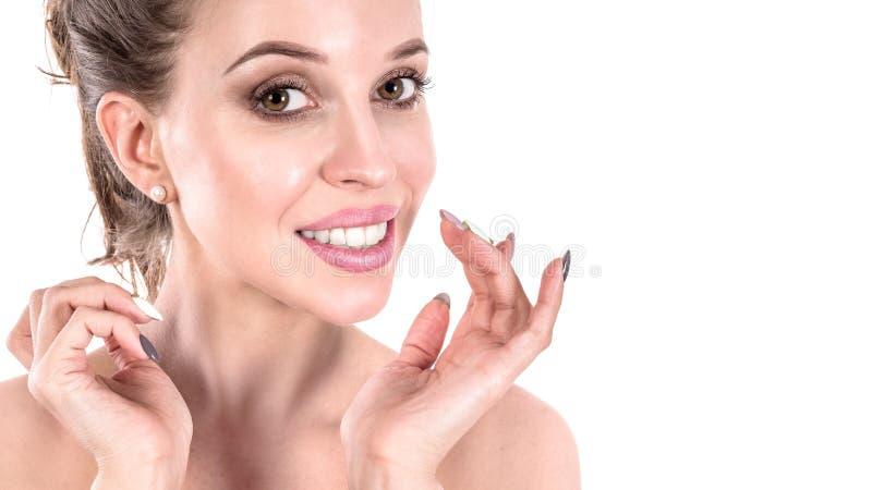 Mujer joven hermosa que aplica el tratamiento poner crema cosmético en su cara en el fondo blanco Concepto del cuidado de piel fotos de archivo libres de regalías