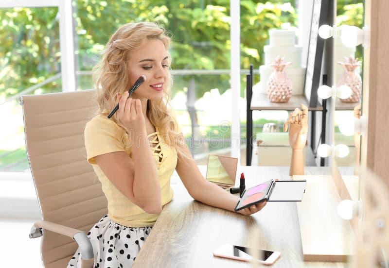 Mujer joven hermosa que aplica maquillaje en frente imagen de archivo