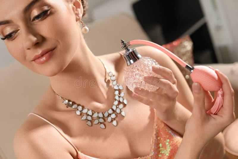 Mujer joven hermosa que aplica perfume dentro fotos de archivo