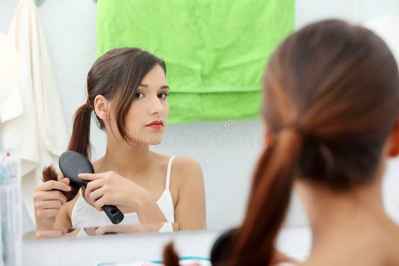 Mujer joven hermosa que aplica su pelo con brocha imágenes de archivo libres de regalías