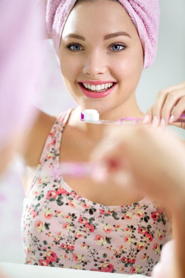 Mujer joven hermosa que aplica sus dientes con brocha fotos de archivo libres de regalías