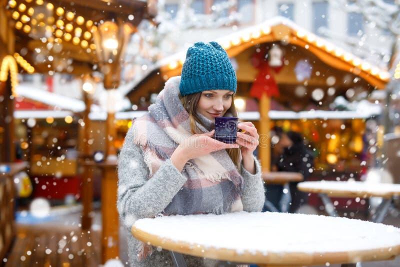 Mujer joven hermosa que bebe el sacador caliente, vino reflexionado sobre en mercado alemán de la Navidad Muchacha feliz en ropa  foto de archivo libre de regalías