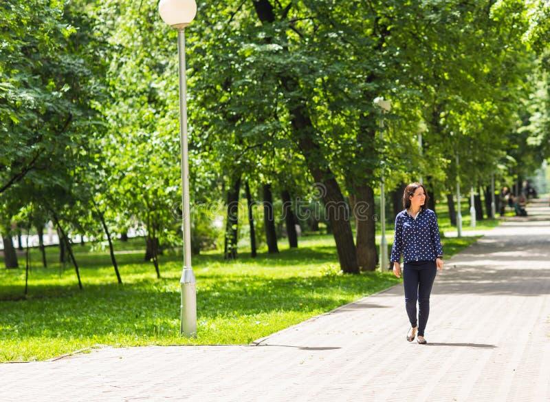Mujer joven hermosa que camina en parque verde del verano imagenes de archivo