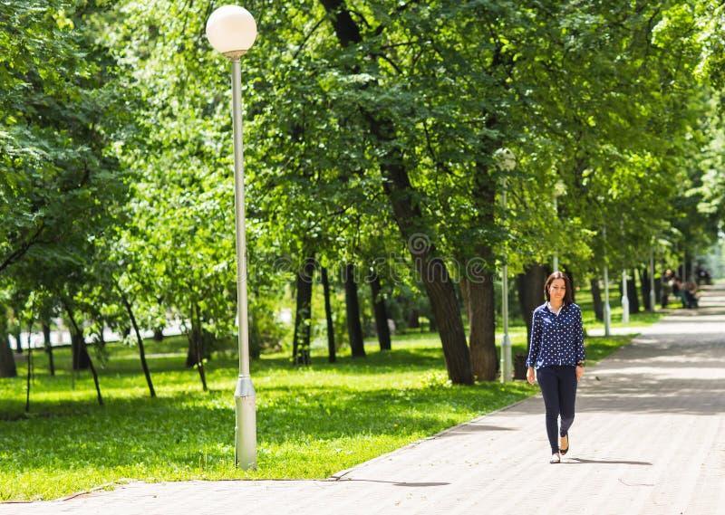 Mujer joven hermosa que camina en parque verde del verano foto de archivo libre de regalías