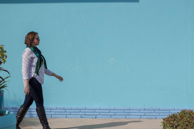 Mujer joven hermosa que camina más allá de un abucheo que lleva de la pared de ladrillo azul imagen de archivo