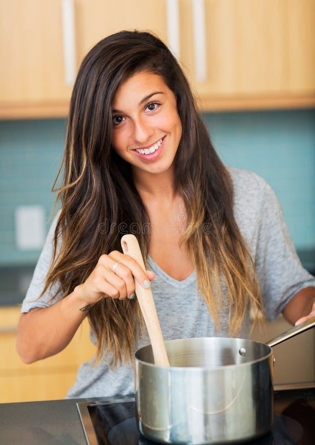 Mujer joven hermosa que cocina la cena imagen de archivo