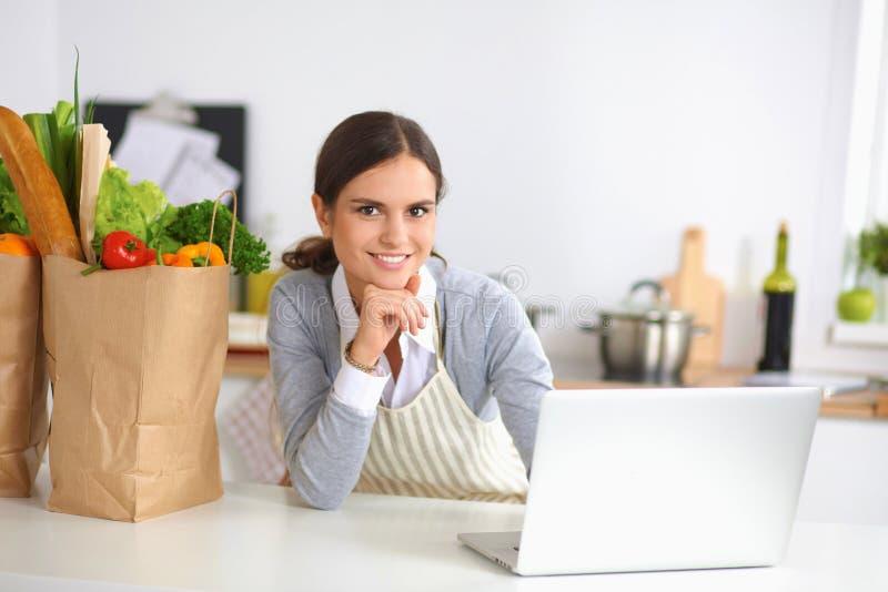 Mujer joven hermosa que cocina mirando el ordenador portátil foto de archivo