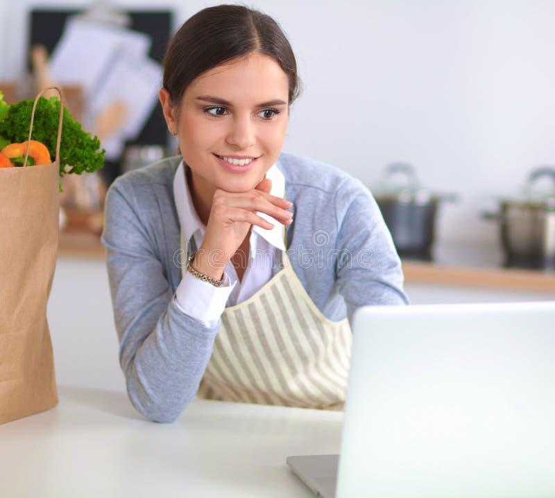 Mujer joven hermosa que cocina mirando la pantalla del ordenador portátil con el recibo en la cocina imagenes de archivo