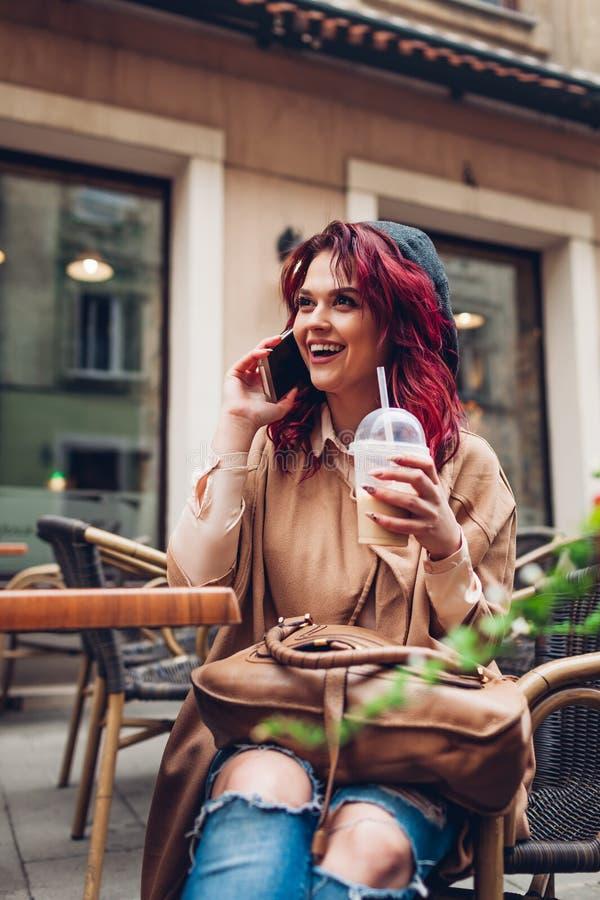 Mujer joven hermosa que come café en café al aire libre mientras que llama a un amigo Muchacha emocionada elegante que usa smartp fotografía de archivo libre de regalías