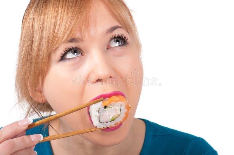 Mujer joven hermosa que come el sushi con los palillos imagen de archivo