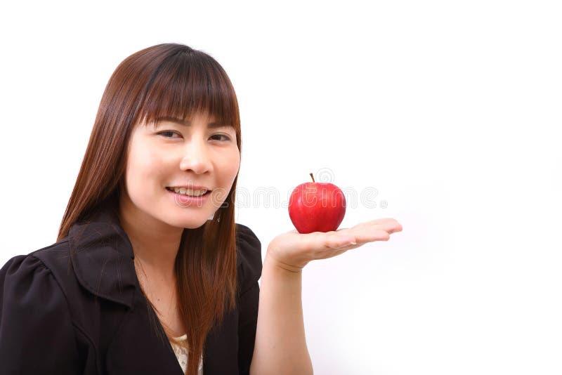 Mujer joven hermosa que come la manzana roja fotografía de archivo
