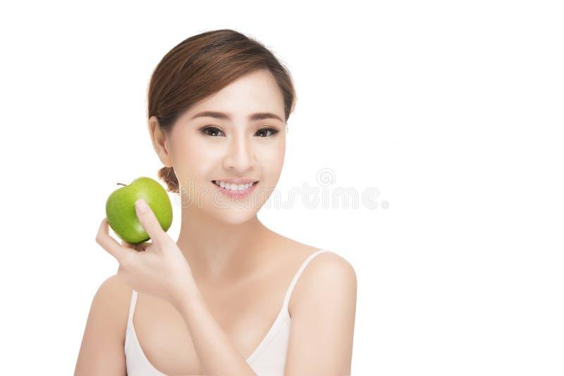 Mujer joven hermosa que come la manzana verde fotografía de archivo