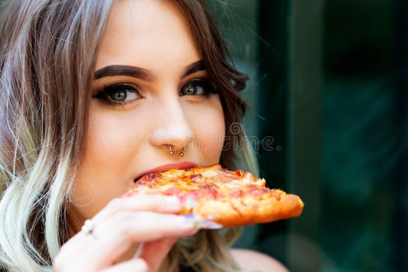 Mujer joven hermosa que come la rebanada de pizza caliente Concepto popular de los alimentos de preparación rápida fotografía de archivo