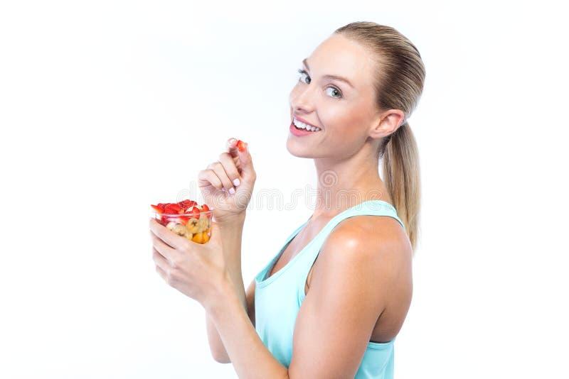 Mujer joven hermosa que come los cereales y las frutas sobre el fondo blanco foto de archivo