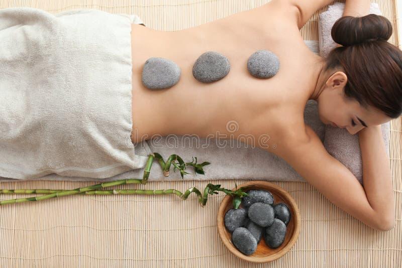 Mujer joven hermosa que consigue masaje de piedra caliente en salón del balneario imagen de archivo libre de regalías
