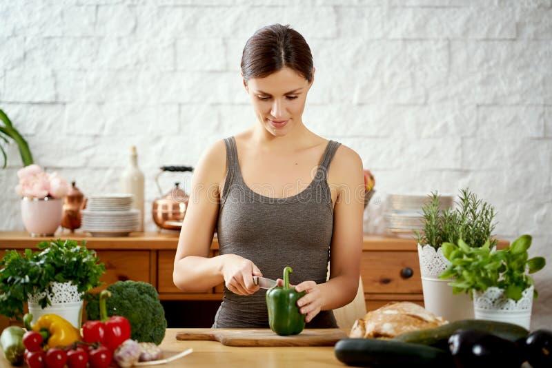 Mujer joven hermosa que corta las pimientas verdes en la cocina en una tabla por completo de verduras foto de archivo