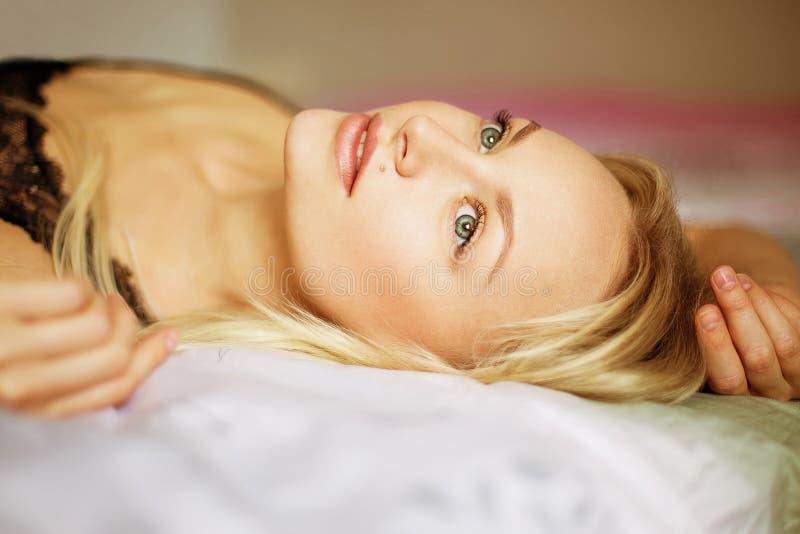 Mujer joven hermosa que despierta en el malo, luz de la mañana fotos de archivo libres de regalías