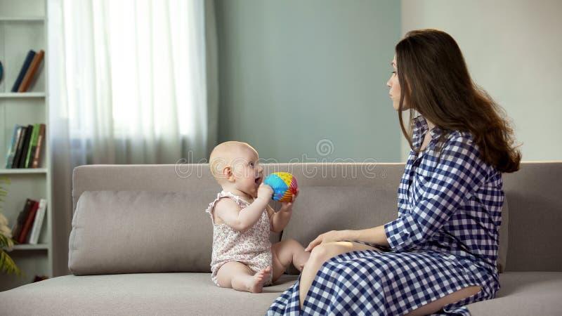 Mujer joven hermosa que disfruta de la maternidad, jugando con el bebé activo, felicidad imagenes de archivo