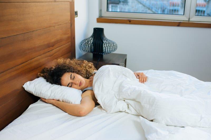 Mujer joven hermosa que duerme en cama fotografía de archivo