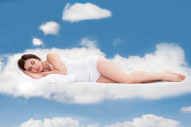 Mujer joven que duerme en las nubes imagen de archivo libre de regalías