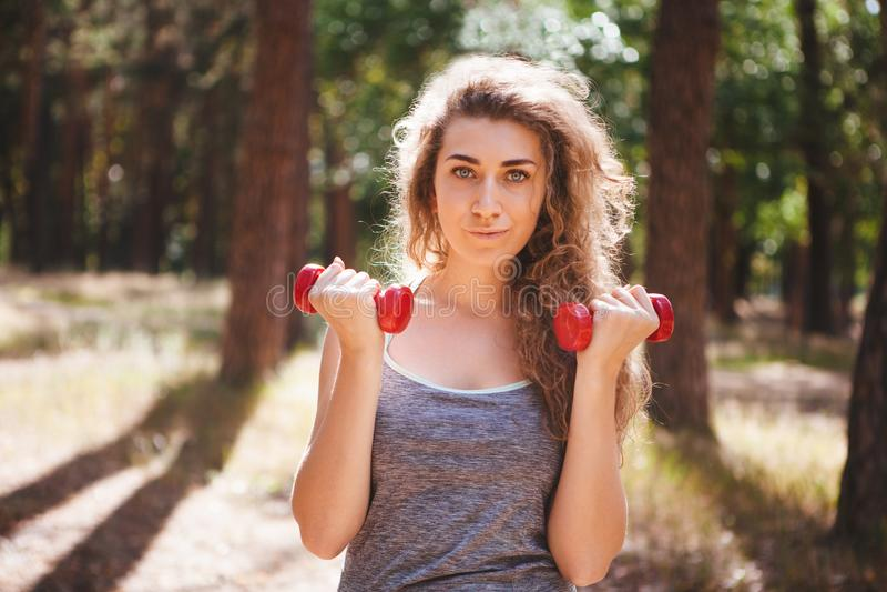 Mujer joven hermosa que ejercita con pesas de gimnasia rojas, deporte de la aptitud en verano foto de archivo libre de regalías