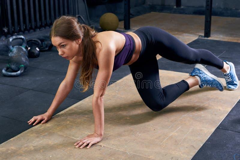 Mujer joven hermosa que ejercita en gimnasio imagenes de archivo