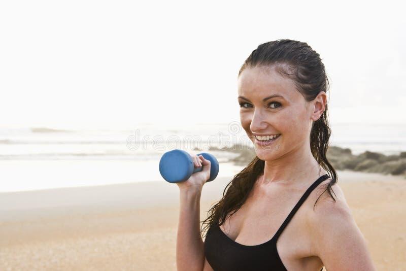 Mujer joven hermosa que ejercita en la playa fotografía de archivo