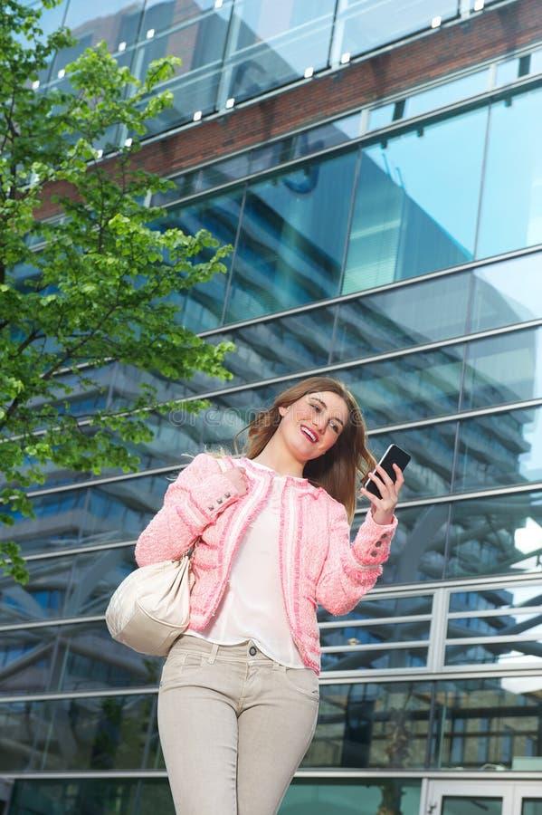 Mujer joven hermosa que envía el mensaje de texto en el teléfono móvil foto de archivo libre de regalías