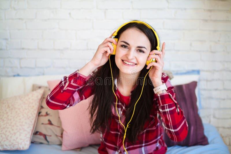Mujer joven hermosa que escucha la música en auriculares en casa imagen de archivo