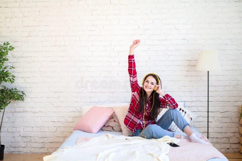 Mujer joven hermosa que escucha la música en auriculares en casa foto de archivo