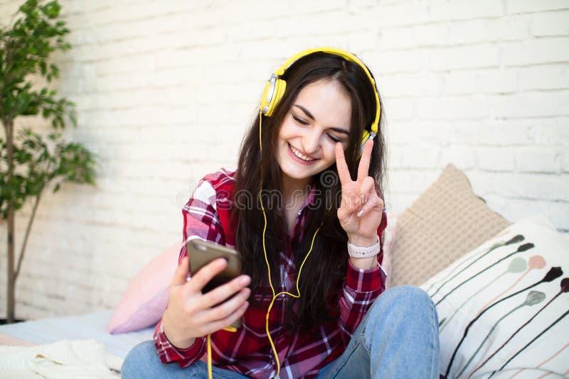 Mujer joven hermosa que escucha la música en auriculares en casa fotografía de archivo
