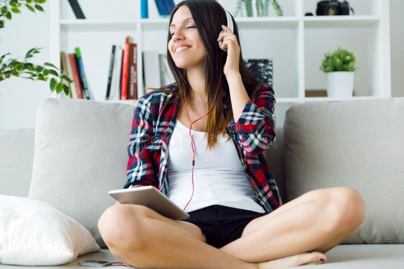 Mujer joven hermosa que escucha la música en casa imagen de archivo