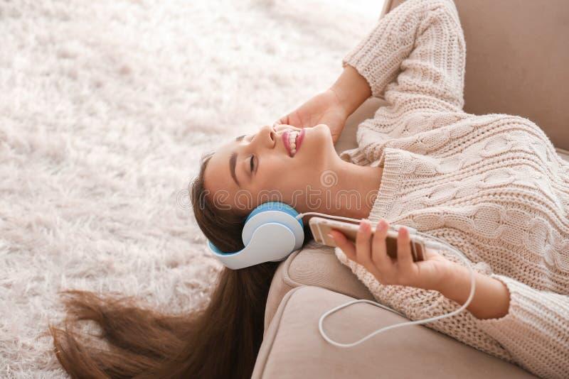 Mujer joven hermosa que escucha la m?sica en casa fotografía de archivo libre de regalías