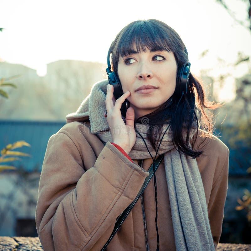 Mujer joven hermosa que escucha los auriculares de la música imagenes de archivo