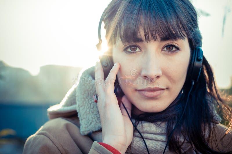 Mujer joven hermosa que escucha los auriculares de la música imagen de archivo
