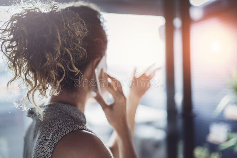 Mujer joven hermosa que habla con los amigos vía smartphone moderno mientras que pasa su tiempo en el café urbano moderno foto de archivo