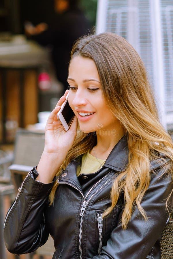 Mujer joven hermosa que habla en smartphone en café al aire libre fotos de archivo libres de regalías